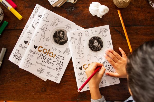 A child colours a Colour Our Story colouring book with a red pencil