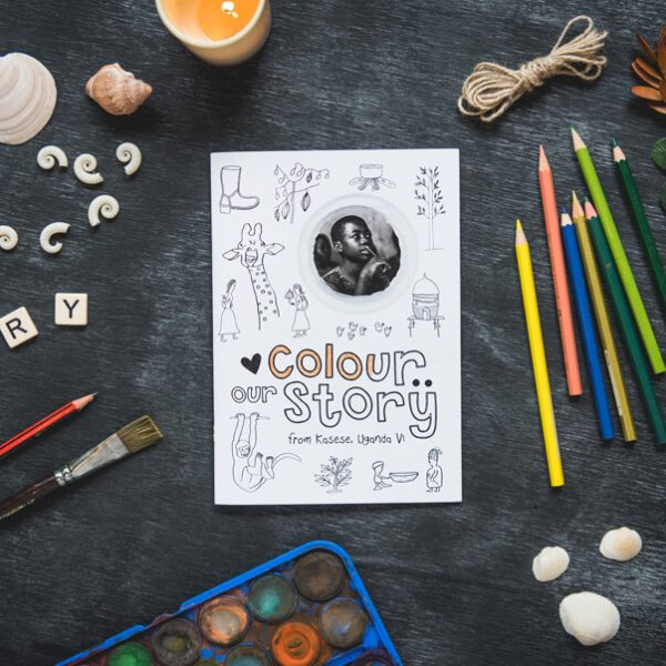 Colour Our Story colouring book surrounded by pencils and art brushes